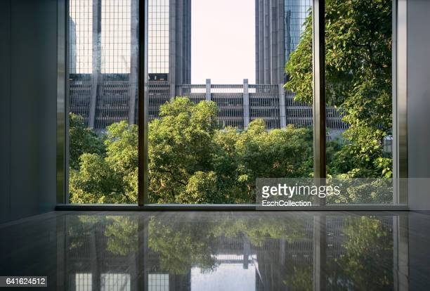 Window view of office facades and green trees