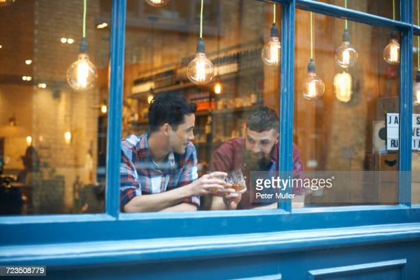 window view of two men raising a glass in public house - pub stock pictures, royalty-free photos & images