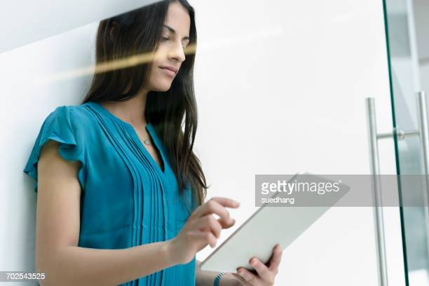 Window view of young businesswoman using digital tablet touchscreen at office entrance