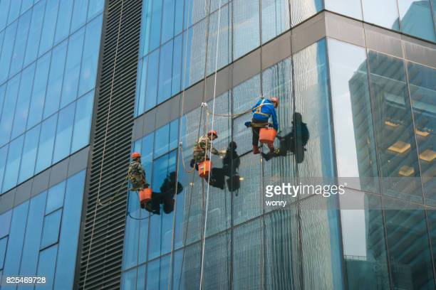 window washers cleaning windows on skyscraper - window cleaning stock photos and pictures