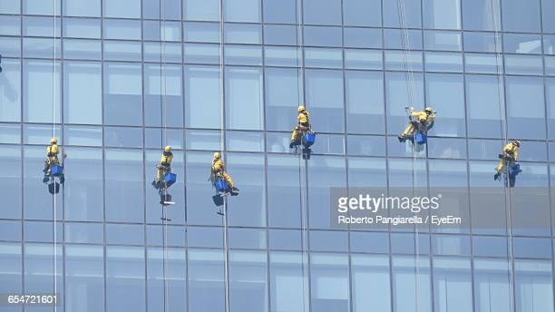 window washers on modern building - window cleaning stock photos and pictures