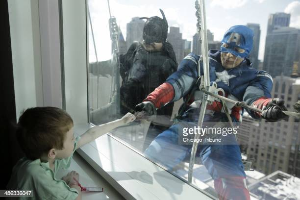 Window washers Pedro Castro as Batman and Roberto Duran as Captain America right entertain patient Zakk Carrier as they hang from rope lines from the...