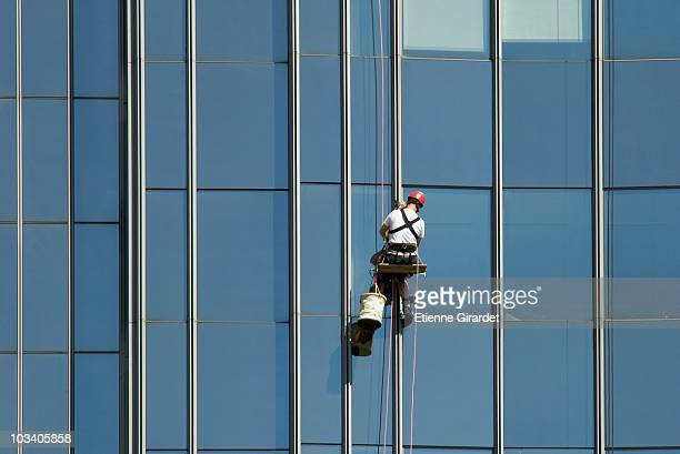 a window washing the windows of an office building - window cleaning stock photos and pictures
