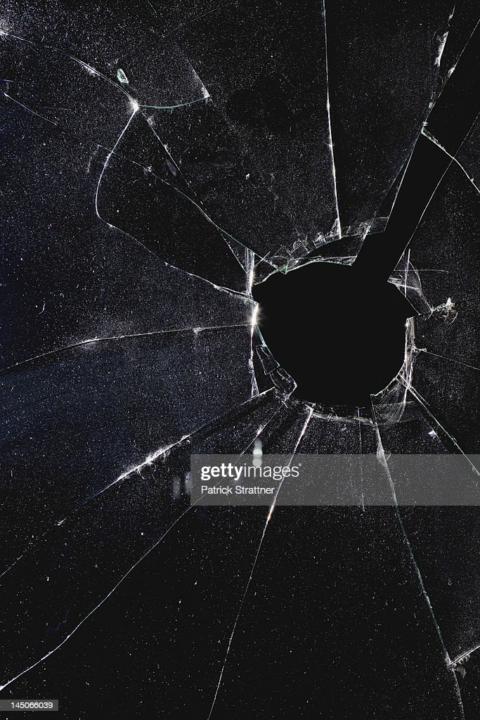 A window with a hole broken through the glass, night : Stock Photo