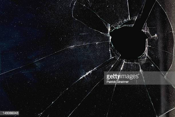 a window with a hole broken through the glass, night - crimine foto e immagini stock
