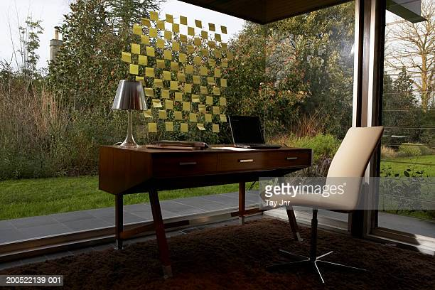 Window with arrangement of adhesive notes by desk