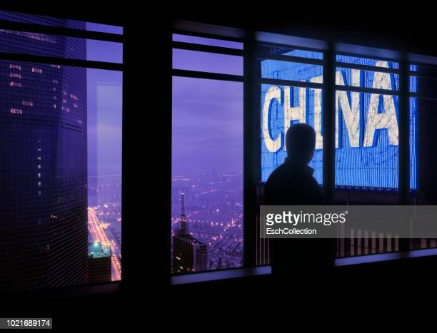 window with man looking at large china neon sign - prosperity stock pictures, royalty-free photos & images