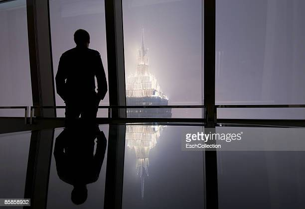 Window with man looking at the skyline of Shanghai