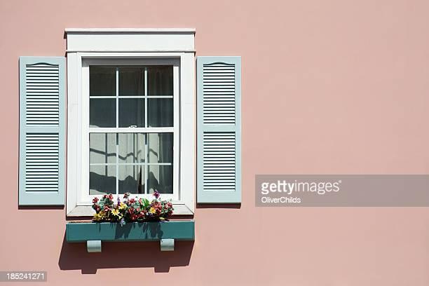 Finestra con sfondo rosa e windowbox.