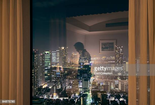 Window with reflection of man and Tokyo skyline