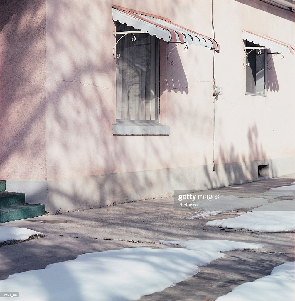 windows covered by awnings overlook snow covered cement sidewalks : Foto de stock