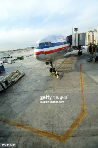 Windshield and nosewheel undercarriage of a Boeing 777-200 parked with choke and an American Airlines towbar with jetway to Gate A22 on apron...