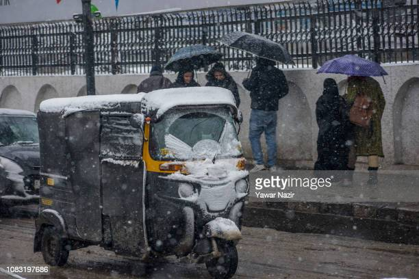 Windshield of an auto rickshaw is covered in snow as it plies on a road during a fresh snowfall on January 16 2019 in Srinagar the summer capital of...