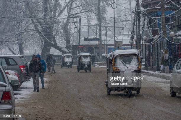Windshields of auto rickshaws are covered in snow as they ply on a road during a fresh snowfall on January 16 2019 in Srinagar the summer capital of...