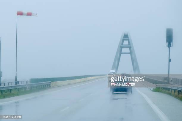 Windsleeve rigidly hangs in the wind as cars drive through the rain over the Fehmarnbelt bridge on the Baltic Sea island of Fehmarn, northern...