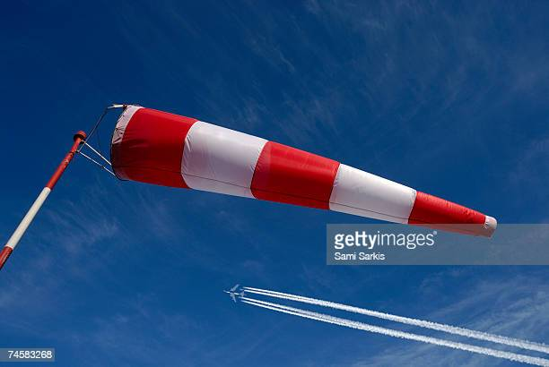 Windsock and airplane against sky, low angle view