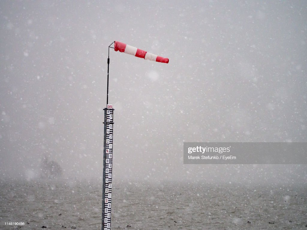 Windsock On Pole In Sea Against Sky During Snowy Weather : Stock Photo