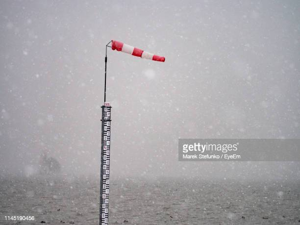 windsock on pole in sea against sky during snowy weather - marek stefunko stock photos and pictures