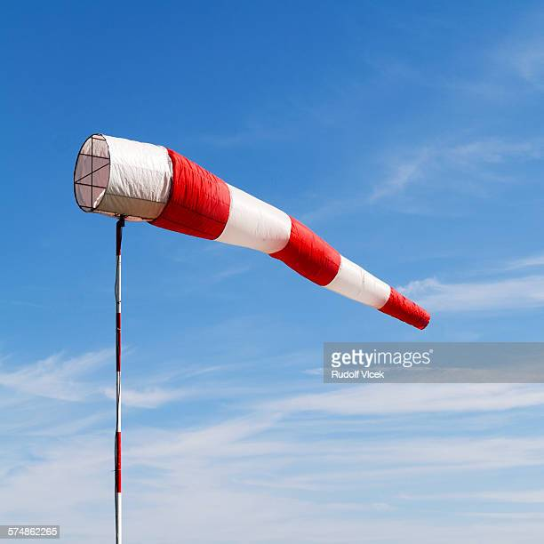 Windsock with red and white stripes, blue sky