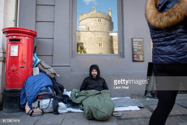Windsor Castle is seen in the reflection of a bank window as Sunny a homeless man who has been on the streets of Windsor for around eight months lays...