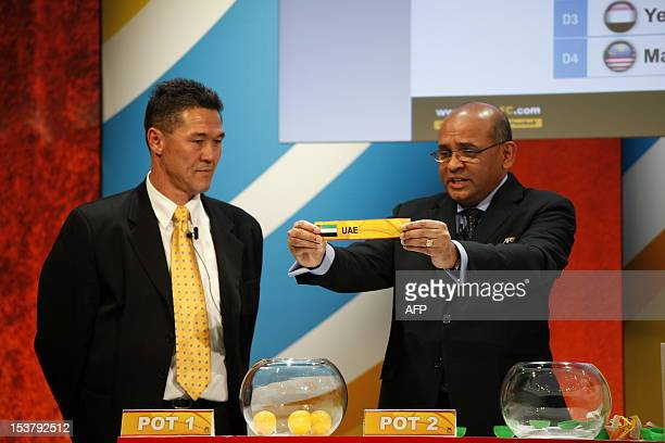 Windsor John AFC executive director displays a draw during the AFC Asian Cup Australia 2015 preliminary draw ceremony as former Australian football...