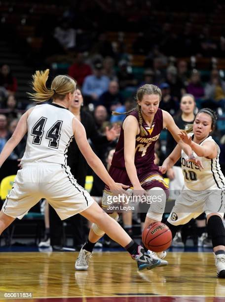 Windsor Madi Denzel drives between Pueblo South Maddie Leigh and Pueblo South Andrea Nelson during their semifinal game on March 9 2017 in Denver...