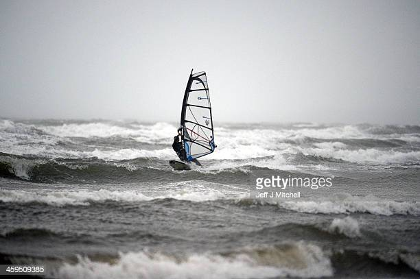 Windsurfer Alan Coutts braves the strong winds at Troon beach on December 27 2013 in Troon Scotland A yellow 'be aware' warning has been issued for...