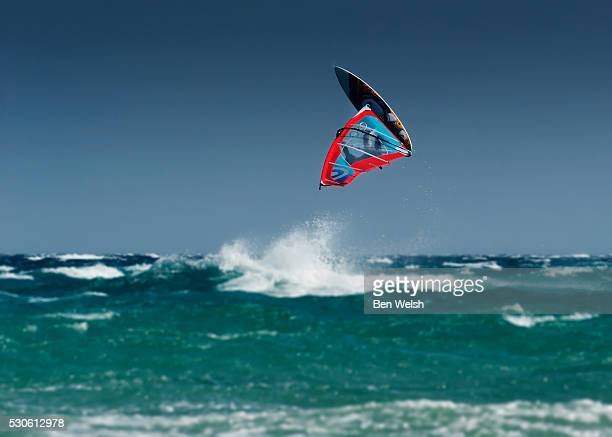 a windsurfer flips upside down above the water off punta paloma; tarifa cadiz andalusia spain - tarifa stock pictures, royalty-free photos & images