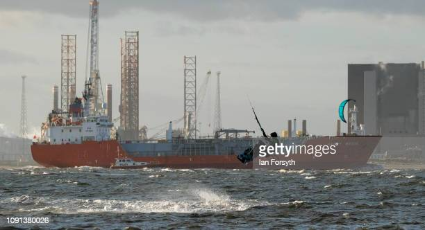 A windsurfer gets some air as he enjoys surfing in strong onshore winds against the industrial backdrop of Hartlepool on January 08 2019 in Redcar...