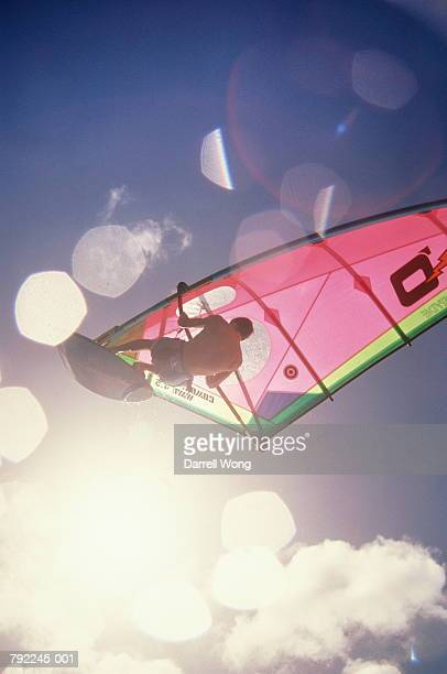 windsurfer jumping in air, low angle view - windsurfing stock pictures, royalty-free photos & images