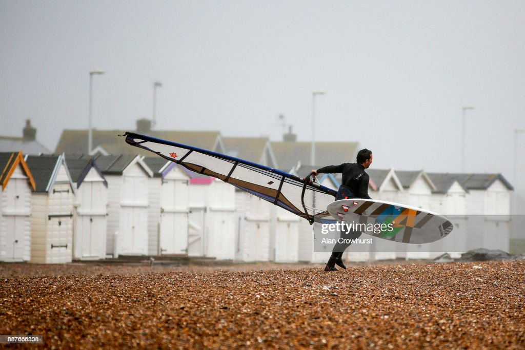 A windsurfer makes his way to the surf as windsurfers and kitesurfers take advantage of the storm force winds off the coast of West Sussex on December 7, 2017 in Goring, England. Storm Caroline is expected to batter the UK with gusts of up to 90mph and poses a potential risk to life, according to the Met Office.
