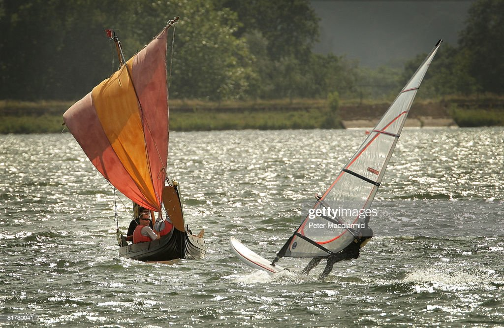 A windsurfer passes replica Norman invasion boat the 'Lille Draken' on Queen Mary's reservoir on June 25, 2008 in London, England. Furniture maker David Jones' reproduction of a 1066 invasion boat has been a three year personal project. Mr Jones hopes to prove that the Bayeux tapestry's detailed embriodery representations of William the Conqueror's invasion ships is correct in it's depiction of a spinnaker type sail.