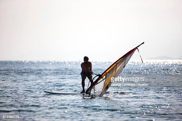 Windsurfer Pulling Sail Out Of The Water