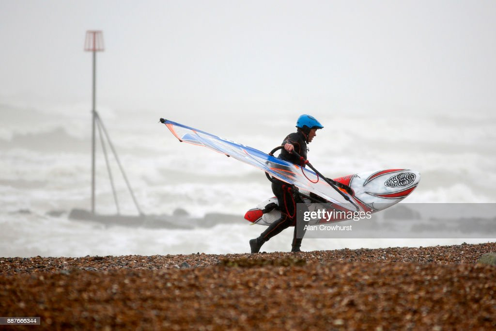 A windsurfer returns from the water as widsurfers and kitesurfers take advantage of the storm force winds off the coast of West Sussex on December 7, 2017 in Goring, England. Storm Caroline is expected to batter the UK with gusts of up to 90mph and poses a potential risk to life, according to the Met Office.