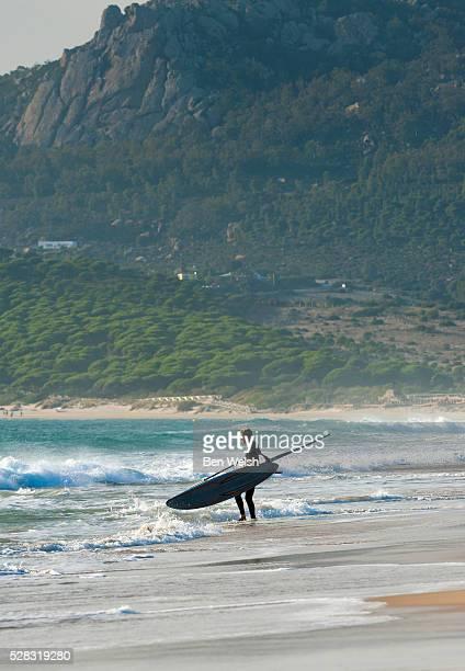 windsurfer standing on the beach; tarifa cadiz andalusia spain - tarifa stock photos and pictures