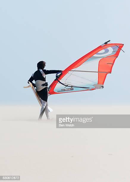 a windsurfer walks on the sand of punta paloma beach with his board; tarifa cadiz andalusia spain - tarifa stock photos and pictures