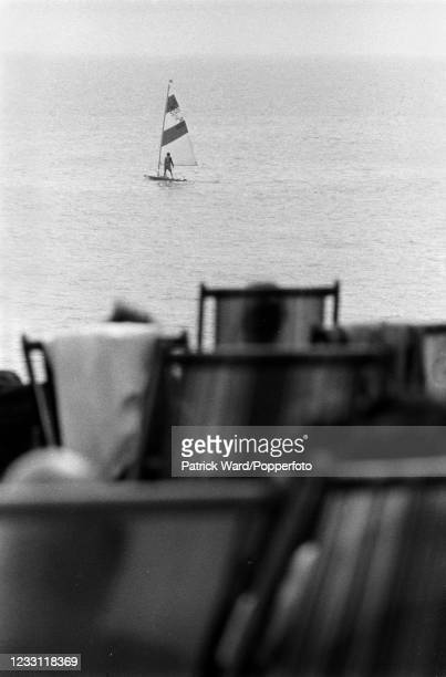 Windsurfer watched by seaside holidaymakers at the beach at Lymington in Hampshire, circa July 1969. From a series of images to illustrate the many...