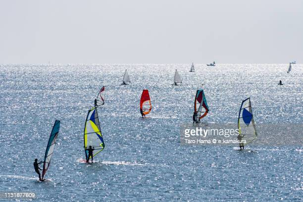 windsurfers and sailing yachts enjoying on the sunny beach in fujisawa city in kanagawa prefecture in japan - shizuoka stock pictures, royalty-free photos & images