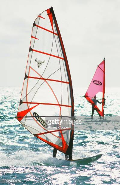 windsurfers off tarifa in southern spain. - sail boom stock pictures, royalty-free photos & images