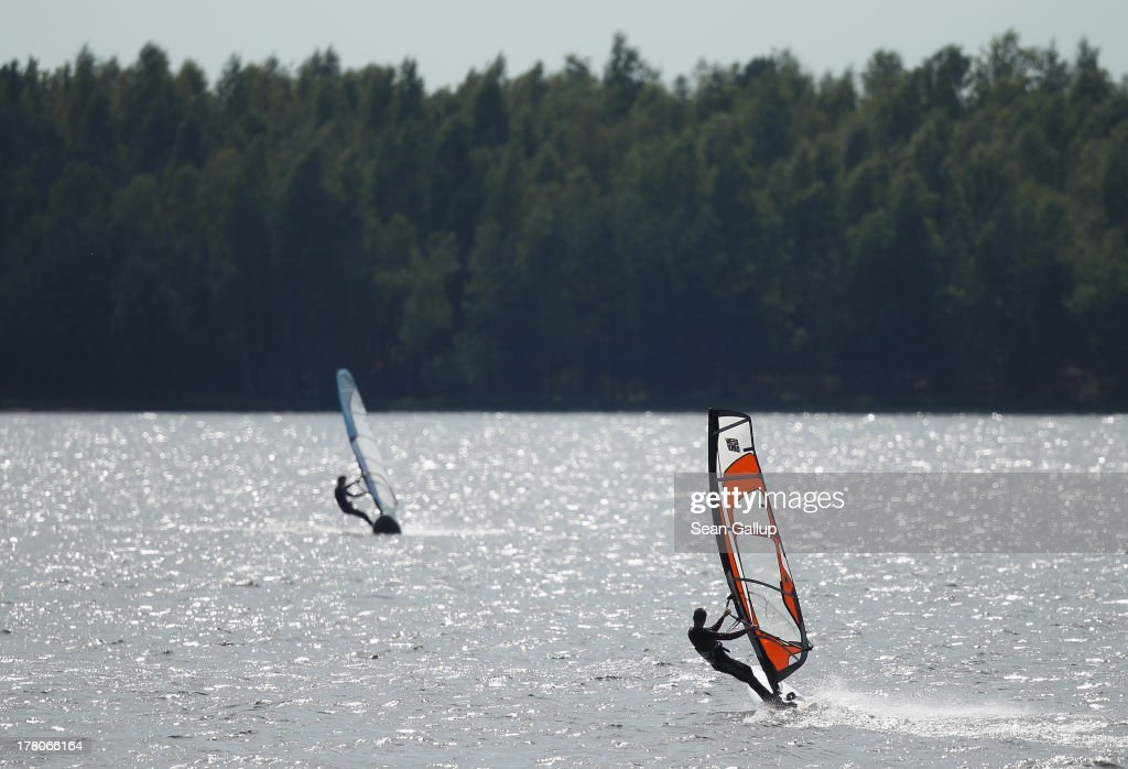 Windsurfers take advantage of a windy day on artifiticial Senftenberger See lake on August 26, 2013 near Senftenberg, Germany. Senftenberger See was once an open-pit lignite coal mine flooded after it shut down in the late 1960s, and today it is popular among tourists, windsurfers and fishermen. In a development project initiated by state government, other nearby former open-pit mines that once evoked a lunar landscape are being turned into lakes in a long-term rejuvenation effort that is also intended to make the area a viable tourist destination. Mineral residue from the mines, however, is proving a difficult stumbling block that is making many of the new lakes too acidic to sustain marine life in the short term.