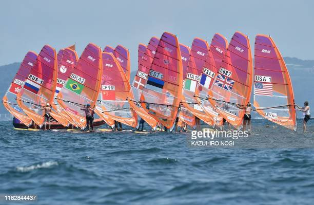 Windsurfers wait for the start the women's windsurfing RSX class competition during a sailing test event for the Tokyo 2020 Olympic Games off the...