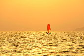 windsurfing at sea red sail against