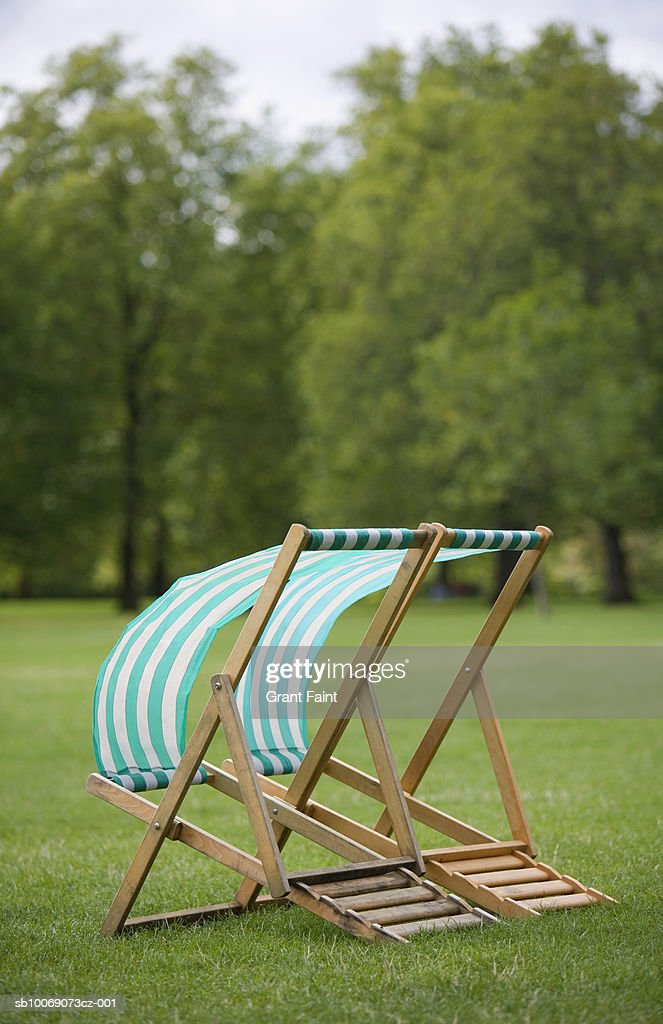 Windswept deckchairs in park : Stockfoto