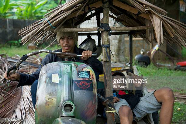Windu and Arief sit in their extreme vespa modification during a scooter festival on June 30 2013 in Cibeureum about 100 km west of Jakarta Indonesia...
