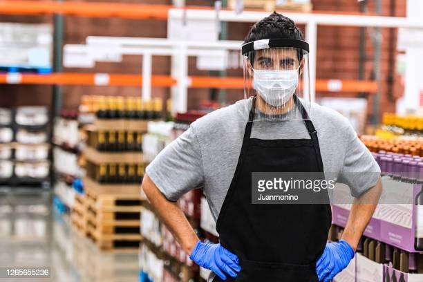 保護フェイスマスクとフェイスシールドを着用したワインおよびアルコール飲料倉庫の従業員 - フェイスシールド ストックフォトと画像