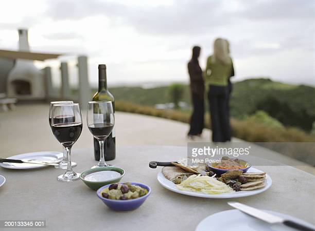 Wine and appetizers on table, three women in  background