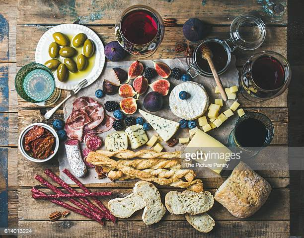 Wine and snack set with various wines in glasses, meat variety, bread, sun-dried tomatoes, honey, green olives, figs, nuts and berries on wax paper over rustic wooden table background