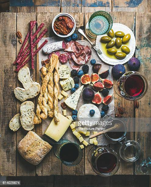 Wine and snack set with various wines in glasses, meat variety, bread, sun-dried tomatoes, honey, green olives, figs, nuts and fresh berries on wax paper over rustic wooden table backgrounds