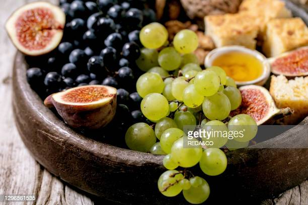Wine appetizers with different grapes. Figs. Walnuts. Bread. Honey and goat cheese on ceramic plate over old wooden background. Close up.