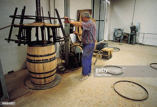 Wine barrels manufacture A man manages a machine that inserts barrels in a cooperage of VegaSicilia company in the Valladolid province
